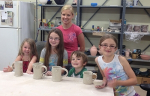 From left to right, students Cadence, Rylie, Tre and Reagan Cataldo are shown with the mugs they created at a recent kids' workshop led by Nickole Bricker, standing, at the Ceramic Arts Center of Waynesboro.